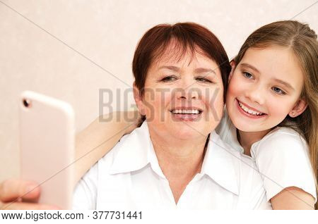 Smiling Cute Little Girl Child And Her Grandmother Are Spending Time Together And Taking Selfie Self