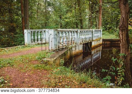 A Small Bridge With Balusters Over A Stream In The Forest. The Architecture Of The 19th Century In T