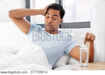 people, bedtime and rest concept - sick indian man lying in bed and dropping medicine pill into glass of water at home