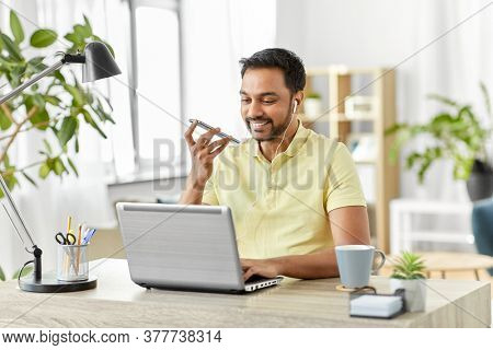 technology, communication and people concept - happy smiling indian with smartphone, earphones and laptop computer using voice command recorder at home office