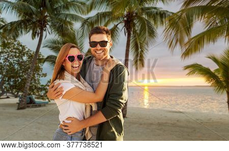 valentine's day, relationships and people concept - happy couple with group of friends hugging over tropical beach background in french polynesia