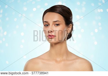beauty, bodycare and people concept - beautiful young woman with bare shoulder over lights on blue background