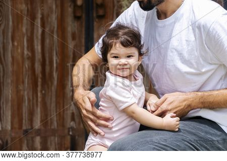 Adorable Little 1 Year Old Girl Learning To Walk With Her Father Helping Balance To Make The First S