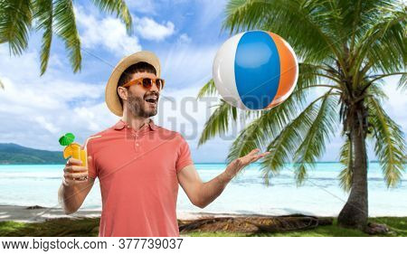 summer, vacation and people concept - happy smiling young man in sunglasses and straw hat with orange juice cocktail and inflatable beach ball over tropical beach background in french polynesia