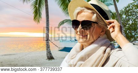 people and leisure concept - portrait of happy senior woman in sunglasses and straw hat over tropical beach background in french polynesia