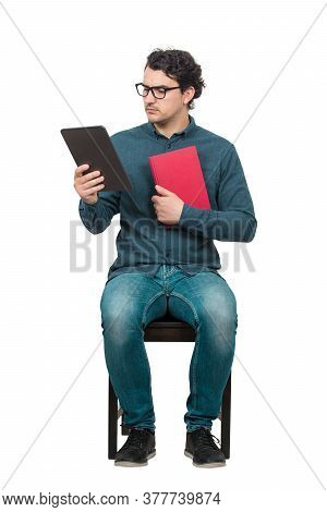 Curious Man Student Or Teacher, Seated On A Chair Using A Pc Tablet While Holds A Red Book. Choosing