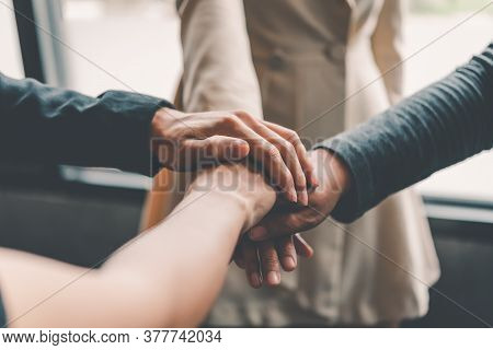 Hands Of Business People Come Together In A Stack Of Hands To Symbolize Collaboration, Teamwork To A