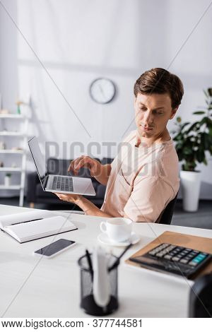 Selective Focus Of Concentrated Freelancer Holding Laptop And Sitting Near Table With Stationery At