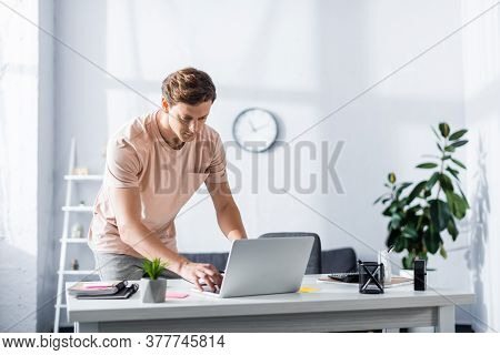 Handsome Freelancer Leaning Forward And Typing On Laptop At Home, Earning Online Concept