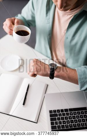 Cropped View Of Freelancer Checking Time On Wristwatch While Drinking Coffee Near Laptop And Noteboo