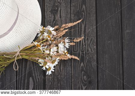 A Bouquet Of White Daisies, Flowers With Dry Ears In A Kraft Paper Vase With A Hat On A Black Wooden