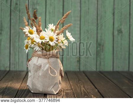 Bouquet Of White Chamomile Flowers With Dry Ears In A Kraft Paper Vase On A Shabby Wooden Background