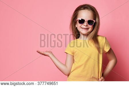 Smiling Frolic 6-7 Y.o. Kid Girl In Yellow T-shirt And Sunglasses Holds Hand Up With Open Palm As If