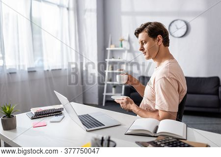 Selective Focus Of Concentrated Teleworker Looking At Laptop Screen While Drinking Coffee At Home, E