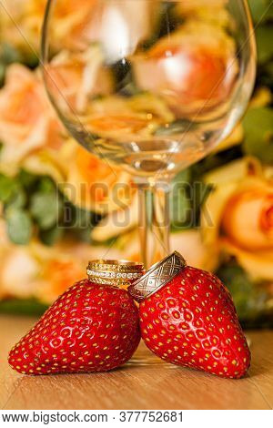 Golden Wedding Rings Of Bride And Groom On Strawberries In Front Of A Glass And A Bouquet Of Roses.