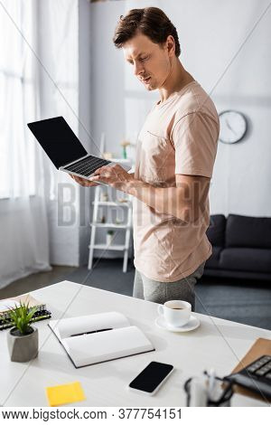 Selective Focus Of Concentrated Man Using Laptop And Looking At Notebook At Home, Earning Online Con