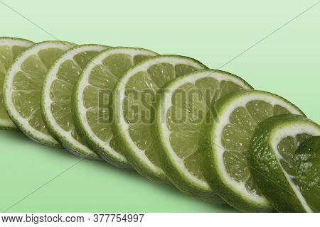 Tahitian Lemon Cut Into Slices On Light Green Background