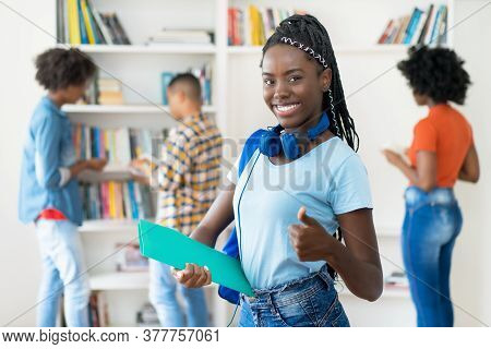 Young African American Female Student With Dreadlocks And Group Of Young Adults Showing Thumb Up At