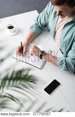 Selective Focus Of Freelancer Checking Time While Writing On Notebook Near Smartphone And Coffee On
