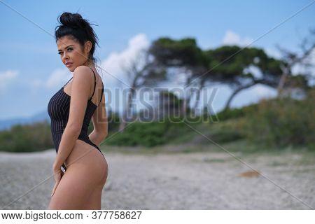 Beautiful latin woman in blue bikini on tropical beach. Portrait of happy young woman smiling at sea. Brunette tanned girl in swimwear enjoying and walking on beach.