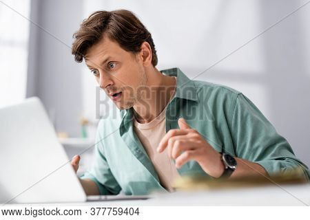 Selective Focus Of Shocked Teleworker Looking At Laptop At Home, Earning Online Concept
