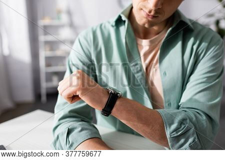 Cropped View Of Young Man Checking Time On Wristwatch At Home, Concept Of Time Management