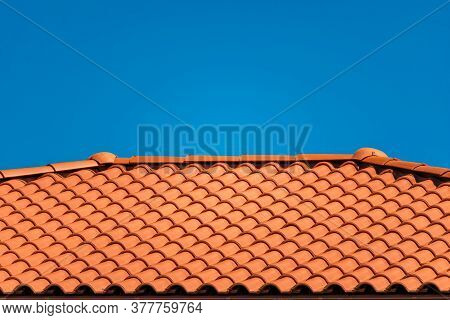 Brown Tile Roof Under Blue Sky. The Photo Is Divided On Two Part. One Part Is A Roof Made Of Clay Ti
