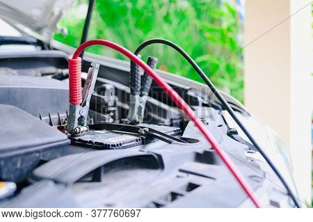The Booster Cables And Discharged Battery, Charging Car Battery With Electricity Trough Jumper Cable