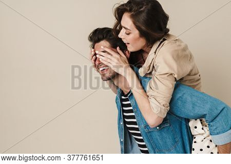 Image of cheerful beautiful couple piggybacking ride and covering eyes isolated over white background