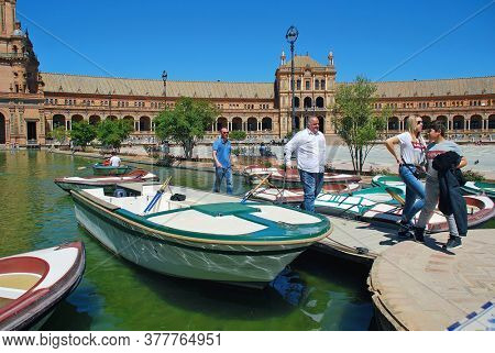 SEVILLE, SPAIN - APRIL 4, 2019: Rowing boats for hire on the moat of the Plaza de Espana. The plaza was built for the 1929 Ibero-American Exposition.