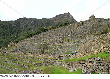 Group Of Visitors Exploring The Ancient Inca Ruins Of Machu Picchu, Unesco World Heritage Site In Cu