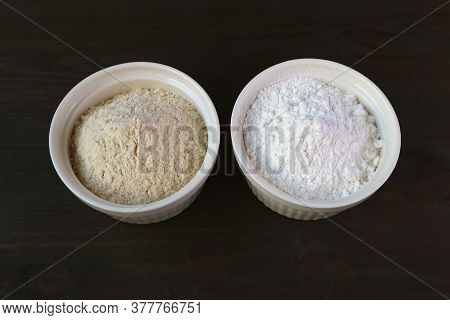 Bowl Of Whole-wheat Flour And A Bowl Of White Flour Isolated On Dark Brown Wooden Table