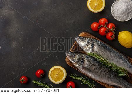 Two Fresh Seabass Fishes With Rosemary And Vegetables On Black Table.