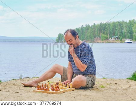 Senior Man Pondering A Move In A Game Of Chess And Sitting On The Beach Near The Lake