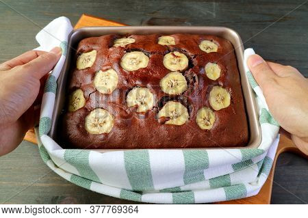 Hand Holding A Pan Of Fresh Baked Delectable Homemade Wholemeal Chocolate Banana Olive Oil Cake