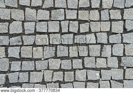 Granite Cobblestone And Small Gravel Pavement Background. Full Frame Of Irregular Cobble. Natural St