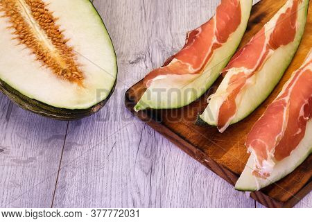 Half White Melon With Nuggets Cut, Sweet And Tasty And Sliced Melon With Iberian Ham On Aged Pine Wo