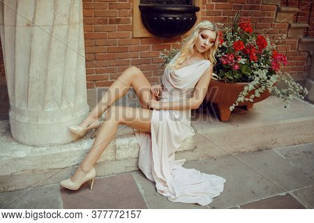 A Long-legged Model, In A Pink Dress With Chic Makeup, Sits In A Historic Castle. Tender Girl On Vac