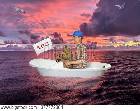 The Man With His Cat Are Drifting In The Bathtub On The Open Sea After Shipwreck. They Hold A Sign T