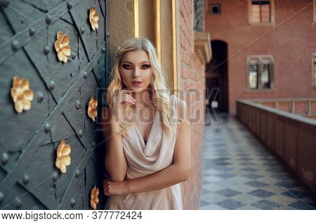 Beautiful Pretty Blonde With Rich Professional Makeup In The Castle. Girl In A Dress Near The Door,