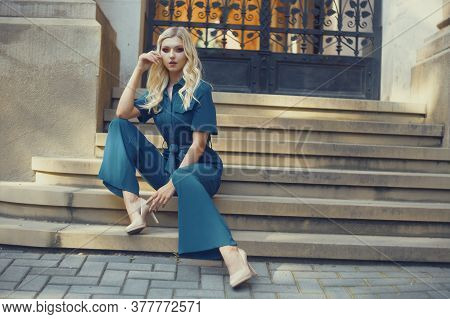 A Full-length Girl Sits On The Stairs In A Long Blue Overalls. Blonde With Gorgeous Red Make-up And