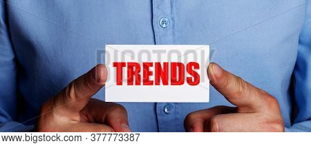 The Word Trends Is Written On A White Card Held By A Man. Trend Concept