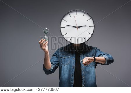 Man With Clock On Head, Wristwatch And Hourglass On Grey Background, Concept Of Time Management