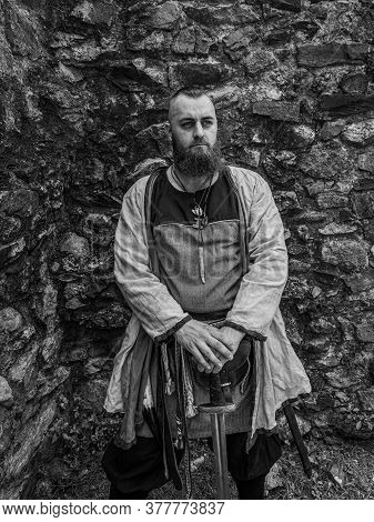 Viking Warrior Portrait With Thick Beard In Front Of A Stone Wall