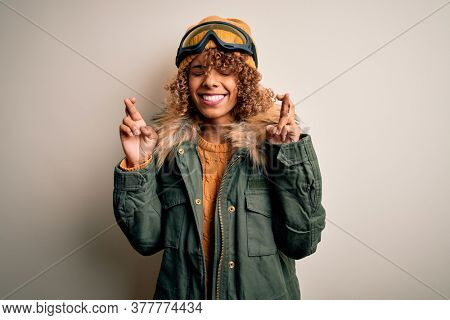Young african american skier woman with curly hair wearing snow sportswear and ski goggles gesturing finger crossed smiling with hope and eyes closed. Luck and superstitious concept.