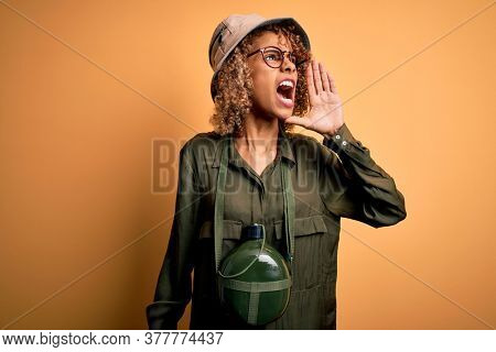 Young african american tourist woman on vacation wearing explorer hat and water canteen shouting and screaming loud to side with hand on mouth. Communication concept.