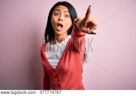 Young beautiful chinese woman wearing casual sweater over isolated pink background Pointing with finger surprised ahead, open mouth amazed expression, something on the front