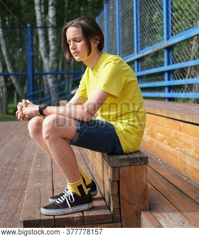 Teenager Boy Sitting On Wooden Stairs On Basketball Playground With Eyes Closed. Serious Hipster Guy
