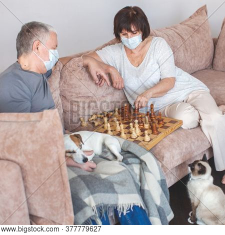 Coronavirus CoVid-19 Couple old aged senior people at home with seasonal winter cold illness disease sit down on the sofa. Elderly couple in medical masks during the pandemic play chess