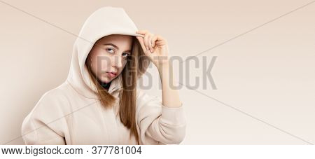 Stylish pretty cool funky teen girl in light sweatshort with hood. Girl teenager wearing trendy hoodie casual clothes. Strong face and long hair. Studio portrait of femle youngster urban style.